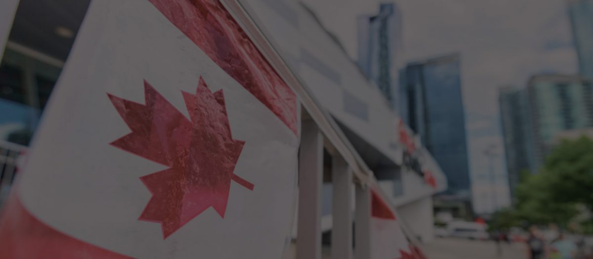 canada plastic flag with blurred urban background in Toronto